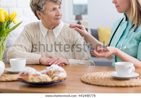 Senior lady sitting at a table with her home nurse, talking together and eating cake