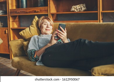 Senior lady with smart phone resting at home