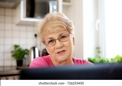 The senior lady surfing the internet with laptop computer