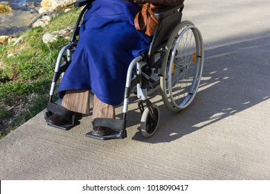 senior lady with wheelchair having a walk in city park in south germany february sunny day at a historical city