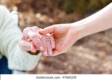Senior Lady in a Wheelchair Holding Hands with her Young Caretaker