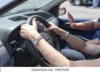 Senior learning to drive a car with a driving instructor.