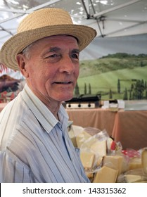 Senior with leghorn at cheese market during Italian days in Bratislava, Slovakia.