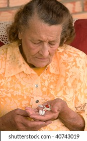 senior looking down at a handful of pills