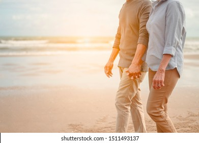 Senior lovers walk hand in hand at the beach at sunset, plan life insurance at retirement concept.