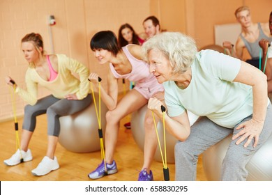Senior making exercise with expanding band during pilates at the gym