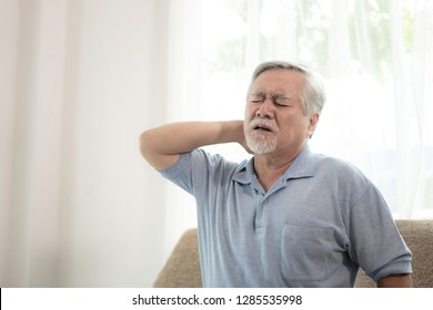 Senior male asian  suffering from bad pain in Neck pain at home - senior unhealth