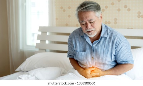 Senior male asian suffering from bad pain in his have a stomachache at home - senior healthcare concept