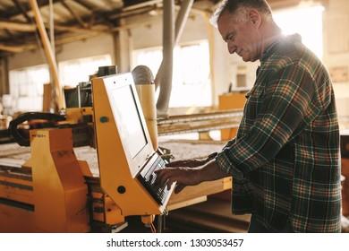 Senior male carpenter programming a cnc wood working machine in workshop. Mature man prepares a computer program for CNC machine at carpentry workshop.