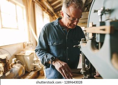 Senior male carpenter working in his workshop. Carpenter cutting wood on machine at carpentry workshop.
