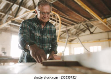 Senior male carpenter working on electric table saw machine cutting wood planks. Skilled mature carpenter working in carpentry workshop.