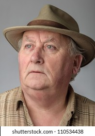 senior male close up portrait in hat, eyes with frown on face