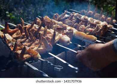 Senior male is cooking summer barbecue with hot chicken wings and pig fat, pork belly or salo close up.  Spring BBQ outdoors.