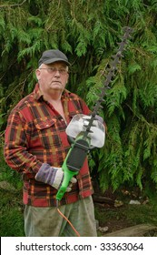 senior male cutting back tree branches in garden with chainsaw