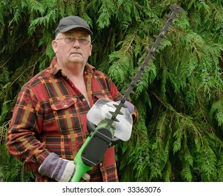senior male cutting back tree branches in garden