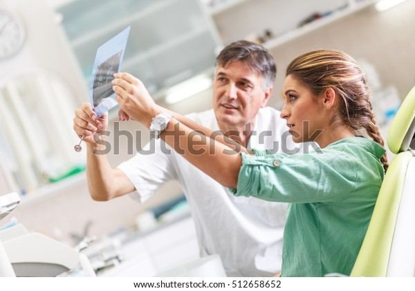 Senior male  dentist in dental office talking with female patient and preparing for treatment.Examining x-ray image.