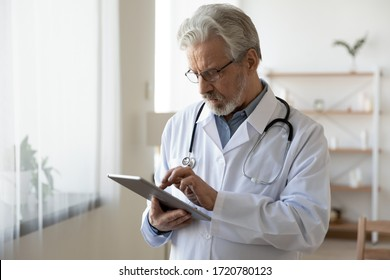 Senior male doctor using digital tablet computer tech providing online healthcare telemedicine ehealth services standing in hospital office. Serious old adult physician consulting remote patient.
