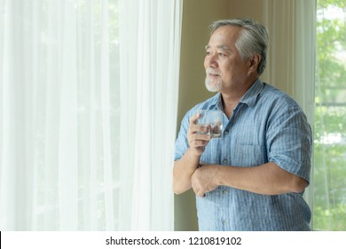 Senior male feel happy drinking fresh water in the morning, enjoying time in his home indoor background - lifestyle senior happiness concept
