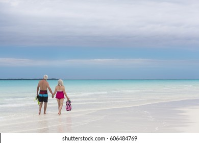 Senior male and female Caucasian couple in swimwear on tropical Caribbean beach with snorkels