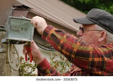 senior male fixing outside light in garden