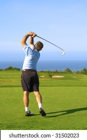 Senior male golfer playing golf from the tee box next to the ocean on a beautiful summer day