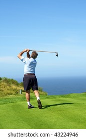 Senior male golfer playing golf from the tee box facing the ocean on a beautiful summer day