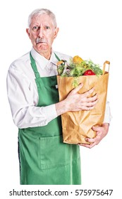 Senior male grocer in a green apron, standing with a bag full of groceries and a look of disgust on his face.