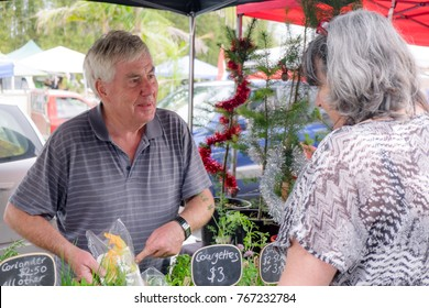 Senior male grower at farmers market smiling and showing organic produce to female customer, with Christmas trees and tinsel in background. Photographed in Kerikeri, Northland, New Zealand, NZ