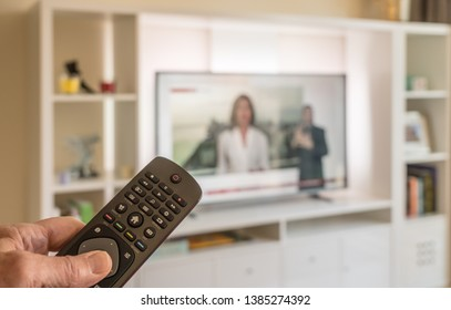 Senior male hand holding TV remote in bright modern apartment with large screen TV