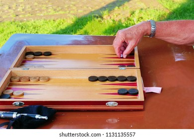 Senior male hand rolls the dice playing backgammon game at an outdoor table