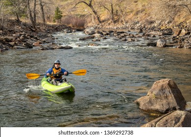 senior male kayaker  is paddling an inflatable whitewater kayak on a mountain river in early spring - Poudre River above Fort Collins, Colorado