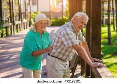 Senior male leans on fence. Elderly couple outdoors. Pains in lower back. Old traumas influence health.