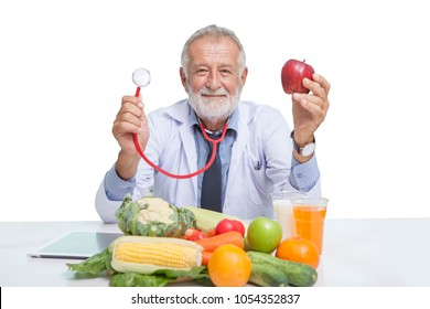 senior male nutritionist holding stethoscope and red apple with Vegetables,Juice,fruit,milk while sitting at table on white background, elderly man dietitian with clipping path