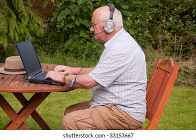 senior male outside using laptop to make voip call