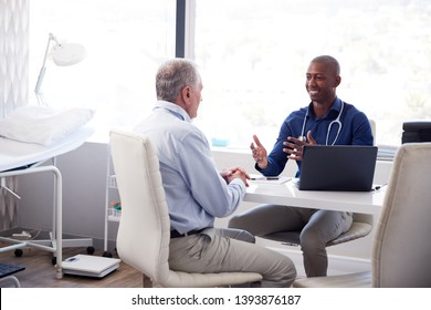 Senior Male Patient In Consultation With Doctor Sitting At Desk In Office