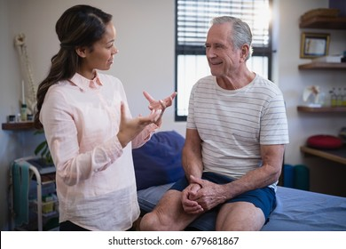 Senior male patient looking at female therapist gesturing while talking in hospital ward