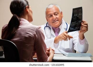 Senior male radiologist explaining x-ray to female patient