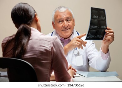 Senior male radiologist showing x-ray to female patient