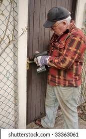 senior male repairing a wooden door latch with drill