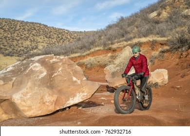 a senior male riding a fat bike on mountain desert trail in Red Mountain Open Space in Colorado, late fall scenery