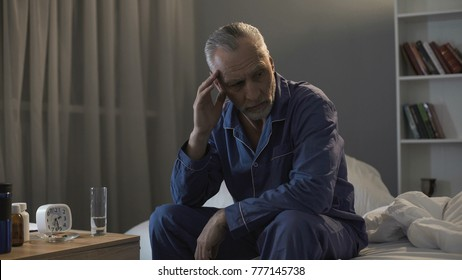 Senior male sitting in bed and suffering from terrible headache at night