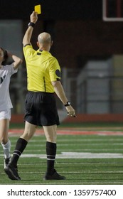A senior male soccer referee, or center referee, issuing a caution, or yellow card, during a match.