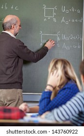 Senior male teacher solving sums on blackboard with students in foreground at classroom