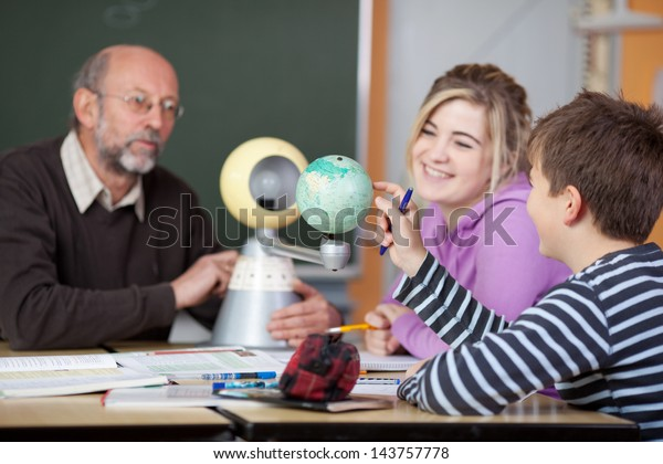 Senior male teacher and students looking at planetarium model at desk in classroom