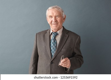 Senior male teacher studio standing isolated on gray wall holding eyeglasses looking camera smiling happy