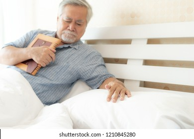 Senior male unhappy is crying, hugging the image of the deceased wife on bed , remember his wife lover - senior sadly concept
