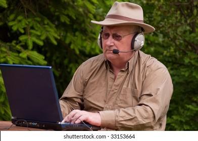 senior male using laptop with headphones