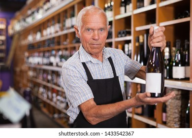 Senior male vintner giving recommendation about purchase wine in his wine house