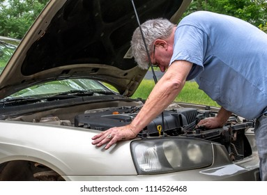 A senior male works under the hood of his car to repair a mechanical issue