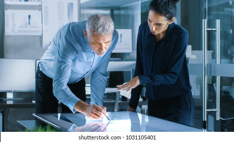Senior Male and Young Female Architectural Designers Draw Building Concept on a Graphics Tablet Display Vertical Touchscreen Table. They Use Gestures for Zooming Project Model.